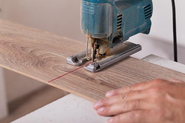 Installing laminate flooring. carpenter cut parquet floor board