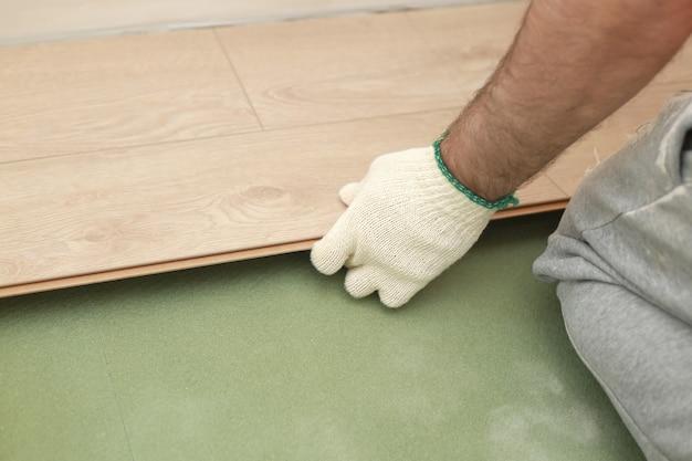 Укладка ламината или паркета в комнате, деталь на руках человека, укладывающая деревянную плитку на зеленую пенопластовую основу.