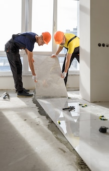 Installing a large ceramic tile.