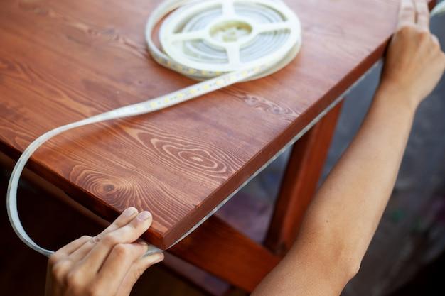 Установка светодиодной ленты для освещения под деревянным столом крупным планом