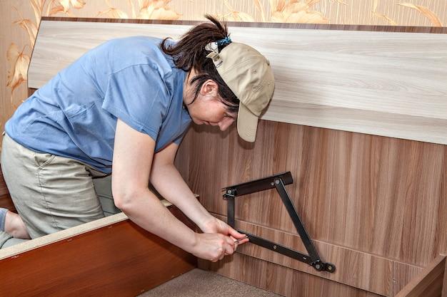 플랫 팩에서 가구를 조립할 때 수납 공간이 있는 침대에 스프링 장착 리프트 메커니즘 설치