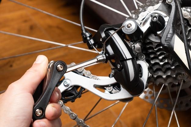 マルチツールを使用して自転車にギアケーブルを取り付ける。