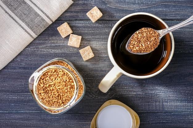 Растворимый кофе. чашка с горячей водой и растворимый кофе ложкой, коричневый сахар на деревянный стол.