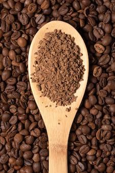 Гранулы растворимого кофе на деревянной ложке на фоне зерен
