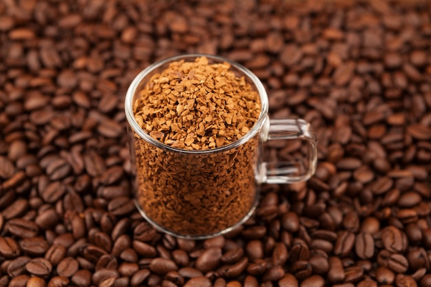 볶은 커피 원두 위에 투명 컵에 담긴 인스턴트, 동결 건조 또는 과립 커피. 차가운 달곤 커피를 만드는 데 사용됩니다.