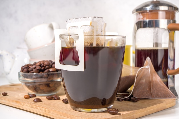 Instant freshly brewed cup of coffee from bag. trendy variety of drip coffee, on white kitchen table with cups, copy space