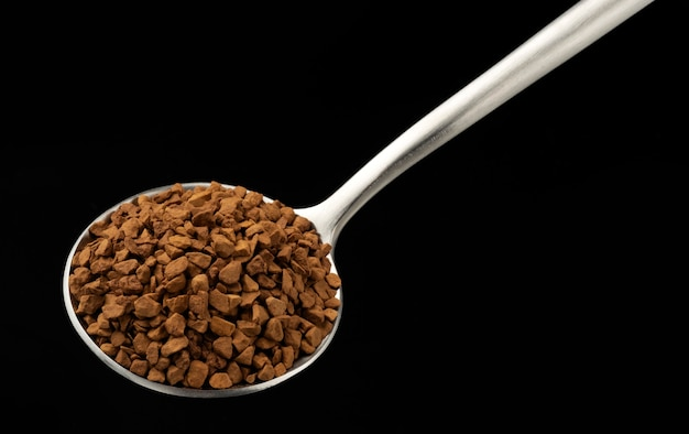 Instant granulated coffee in spoon on black background, top view