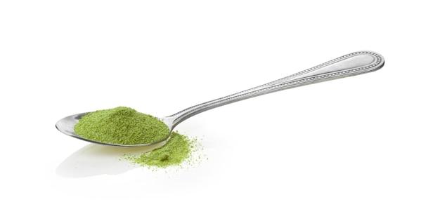 Мгновенный порошок зеленого чая в ложке, изолированные на белом фоне