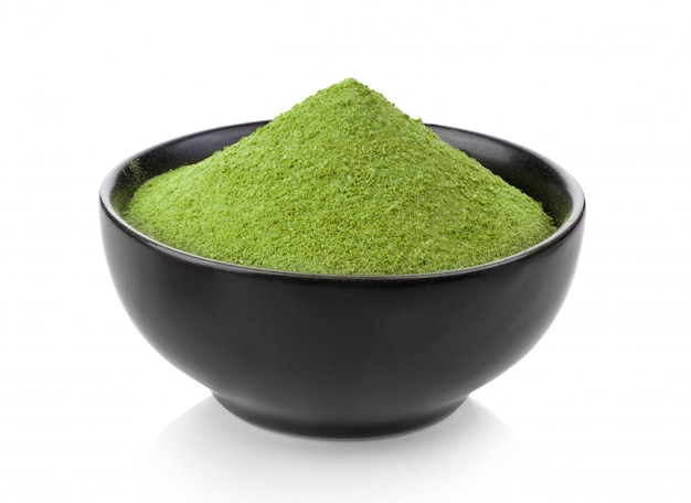 Instant matcha green tea in black bowl on white