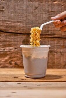 Лапша быстрого приготовления, азиатский фаст-фуд, чашка лапши на деревянных фоне.