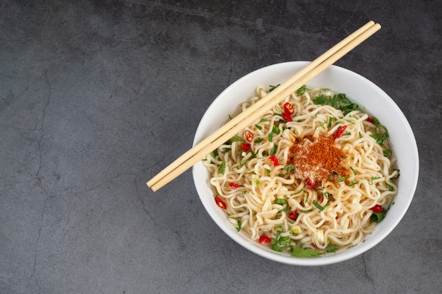 Instant noodle ready to eat with chopsticks in cup  on black wall.