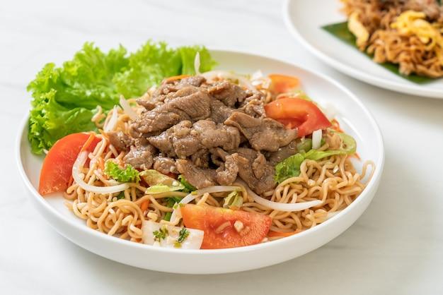 하얀 접시에 돼지 고기와 인스턴트 국수 매운 샐러드-아시아 음식 스타일
