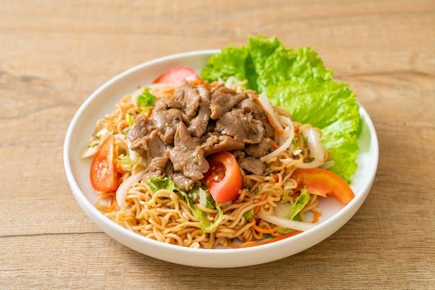 白い皿に豚肉のインスタントラーメンスパイシーサラダ-アジア料理スタイル