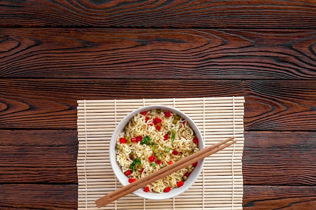 Instant noodle with pepper, peas, chopstick and greens
