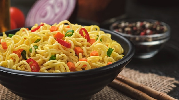 Instant noodles on black background, served with vegetables and herbs, spicy asian lunch