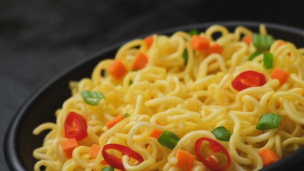 Instant noodles on black background, served with vegetables and herbs