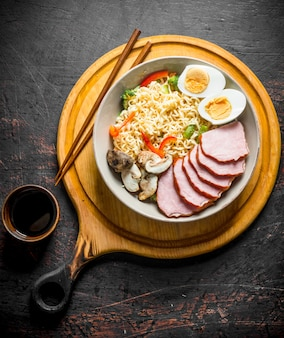 Instant noodles in bowl on cutting board with becon, egg and mushrooms.