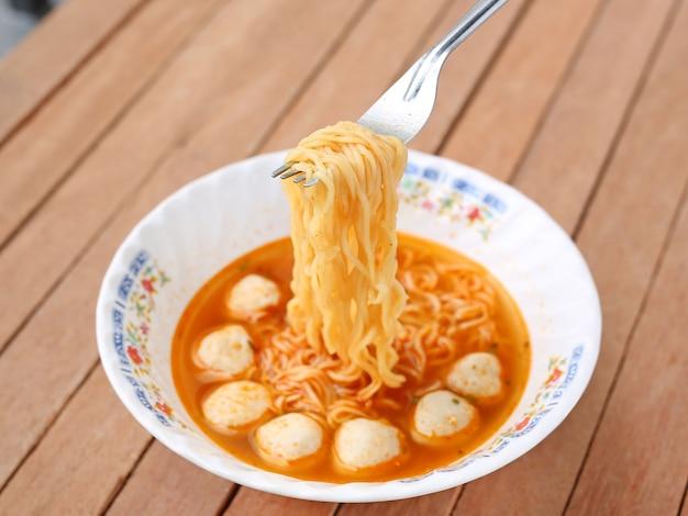 Instant noodles in ceramic bowl against wooden plank.