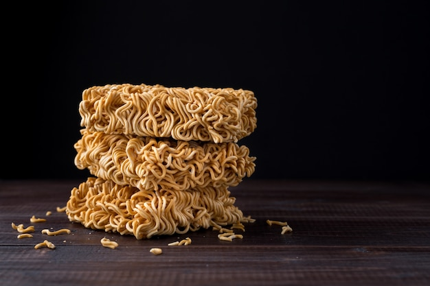 Instant noodles close up on wooden table over black background with copy space