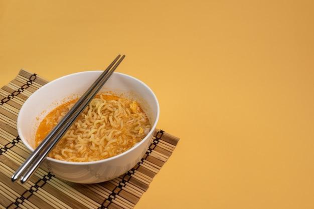 Лапша быстрого приготовления, приготовленная в мисках и палочками для еды, готова к употреблению в качестве основного блюда или закуски.