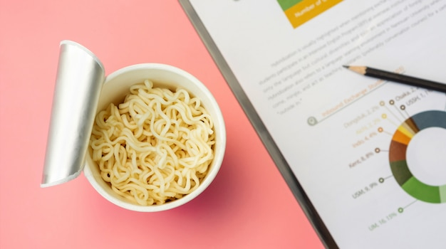 Instant noodles cup and document sheet on a pink background.
