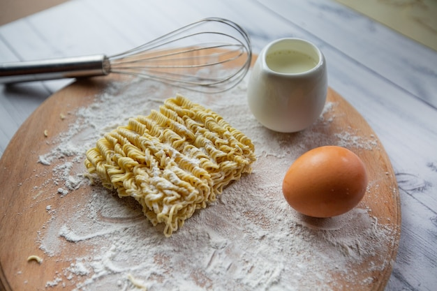 Instant noodles eggs milk and a whisk view from above selective focus