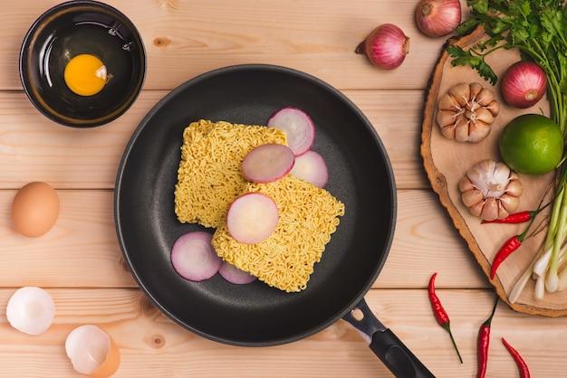 요리를 위한 인스턴트 국수와 나무 배경에 계란과 야채와 함께 접시에서 먹습니다.