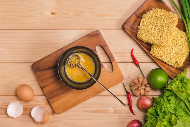 요리를 위한 인스턴트 국수와 휘핑된 계란과 야채를 나무 배경에 넣은 접시에서 먹습니다.