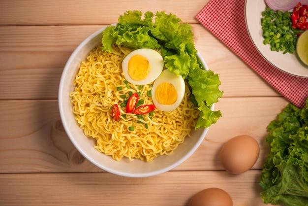 Лапша быстрого приготовления в миске с овощами и вареным яйцом на деревянном фоне