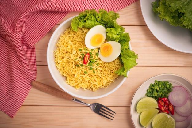 나무 배경에 야채와 삶은 달걀을 넣은 그릇에 인스턴트 국수