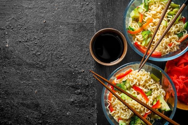 야채, 생강, 간장을 곁들인 그릇에 담긴 인스턴트라면.