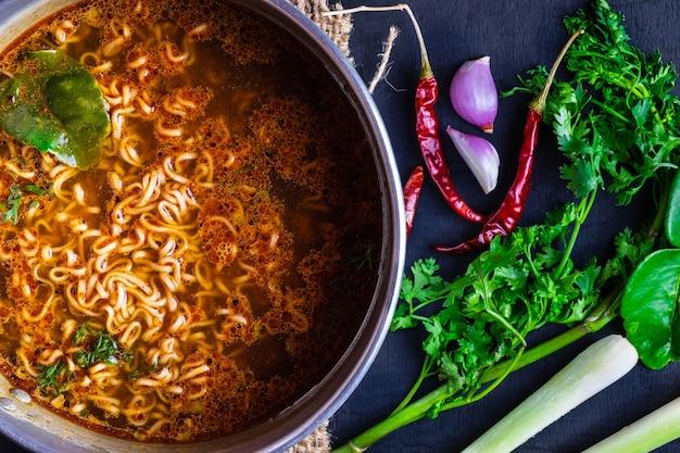 スパイシーな鍋にスパイスや野菜を入れたインスタントラーメン。