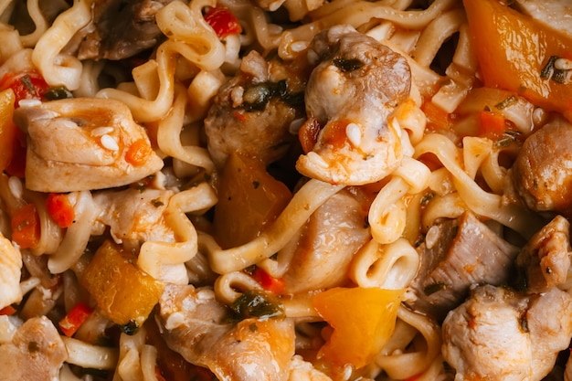 Instant noodles or pasta with vegetables and chicken meat with sauce. traditional asian food close-up