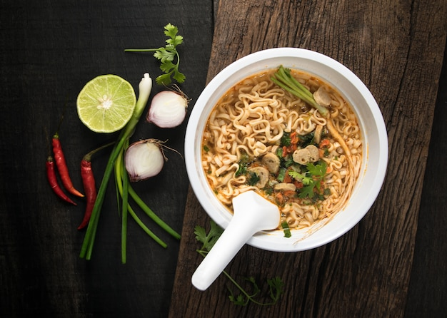 Instant noodles in plastic bowl and vegetable side dishes on wood background.