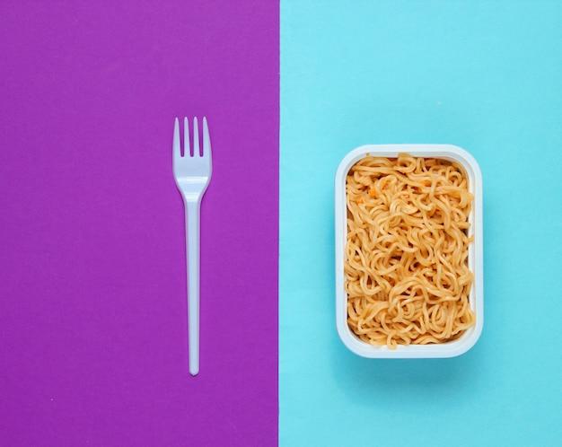 Instant noodles and plastic fork on purple blue background