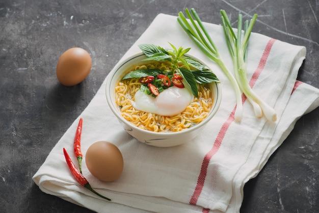 В суп с лапшой быстрого приготовления положить яйцо и овощи