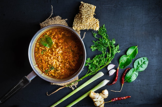 Instant noodles in spicy pot with spices and vegetables.
