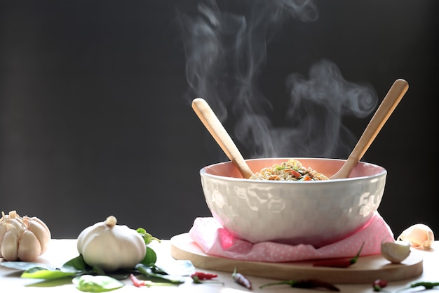 Instant noodles and spoon with wooden fork in cup with smoke rising and garlic