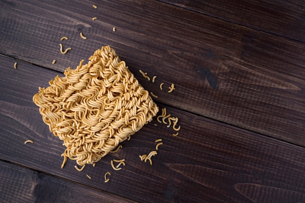 Instant noodles in top view closeup on wooden table with copy space