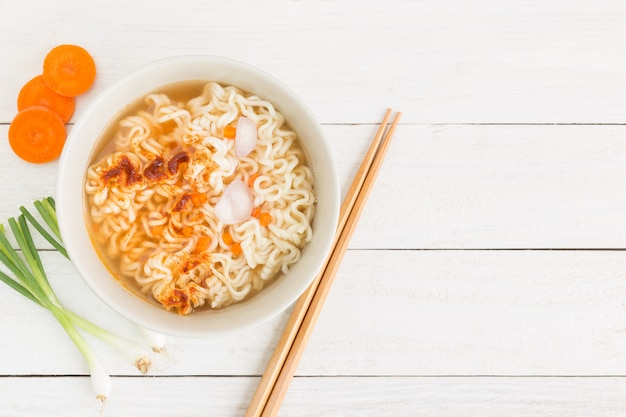 Instant noodles and vegetables on white wooden background