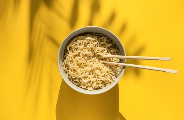 Instant noodles with chinese chopsticks on yellow background. top view egg noodles.