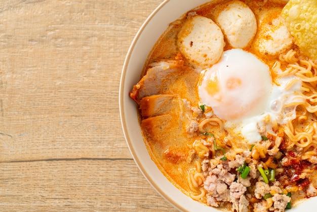 Лапша быстрого приготовления со свининой и фрикадельками в остром супе или лапша том ям по-азиатски