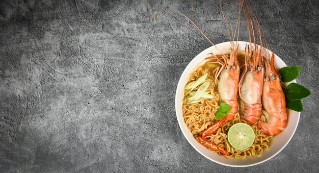 Instant noodles with prawn spicy soup bowl lime / cooked seafood with shrimp soup dinner table and spices ingredients thai food asian traditional