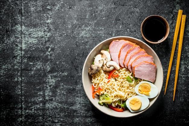 黒の素朴なテーブルに野菜、卵、ハム、醤油、箸を使ったインスタントラーメン