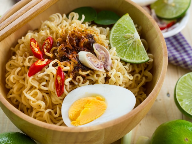 Instant noodles in wooden bowl and vegetable side dishes on wood table