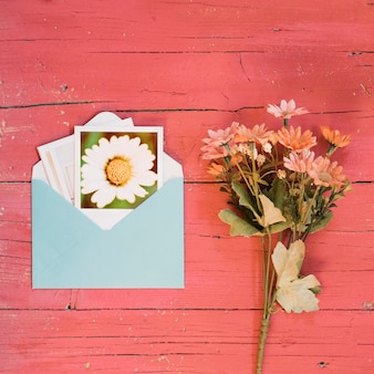 Instant photos in an envelope with bouquet of daisies