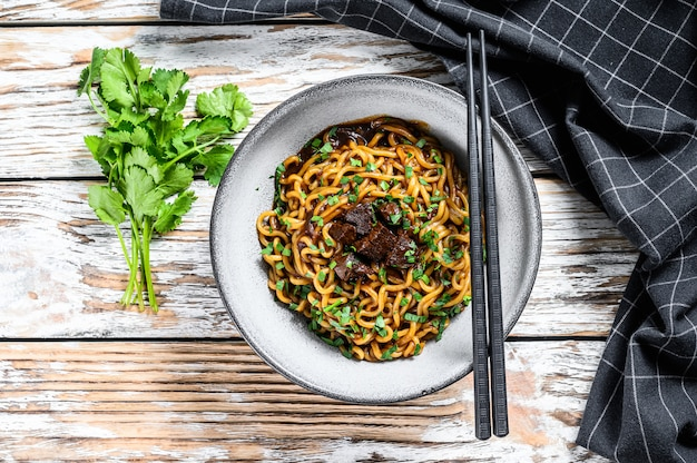 Instant ramen noodles with coriander and tofu in a cast-iron pot. vegetarian dish. white wooden background. top view