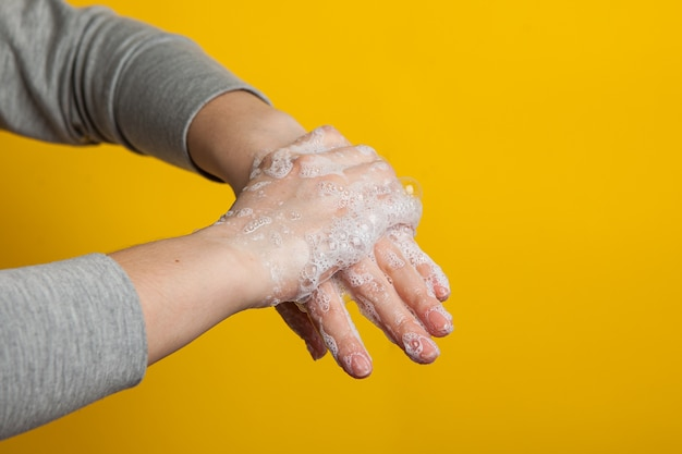 Instruction to carefully wash your hands and nails . women's hands in a soap solution on a bright background