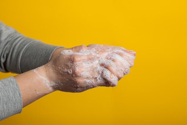 黄色の背景に手と爪を注意深く洗うための指示。明るい背景のクローズアップで石鹸液の女性の手。