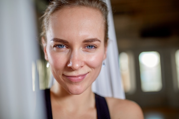 Instructor in aerial yoga portrait close-up. hipster girl with an expressive look yoga trainer posing for the camera